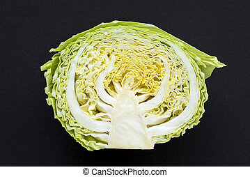 half cabbage on black - half of fresh green cabbagehead...