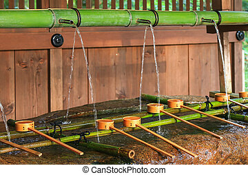 Water running out through bamboo pipe to water basin at...