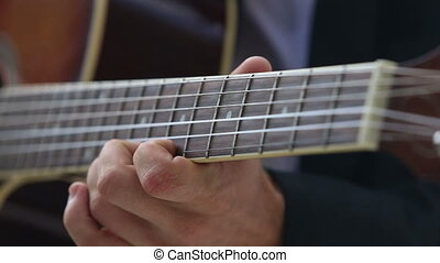 european man plays guitar chords on fingerboard - european...