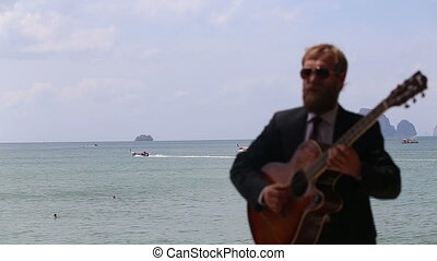 european man plays guitar against sea with focus on boats -...