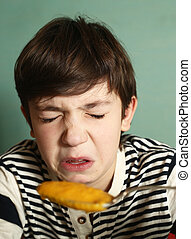 boy eat pumpkin soup with expression of disgust - preteen...