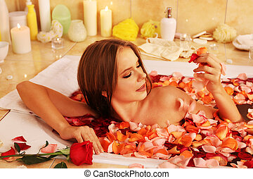 Girl taking bath with rose petals in bath.