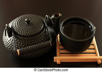 Black teapot - Black oriental teapot and cup on dark wooden...