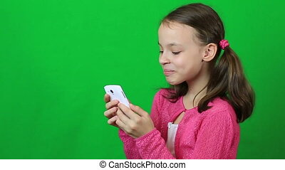 Little girl writing short message on mobile phone on green...