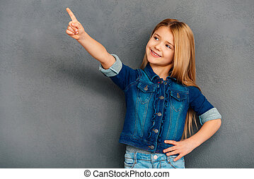 Take a look here Cheerful littlegirl pointing away and...