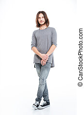 Full lenght of handsome young man with long hair standing...