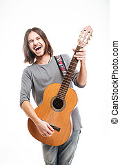 Excited handsome young man with long hair playing acoustic...