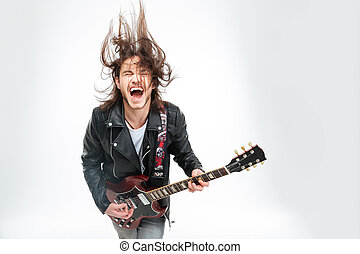 Excited young man with electric guitar shouting and shaking...