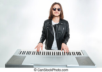 Smiling man with long hair in sunglasses playing on...