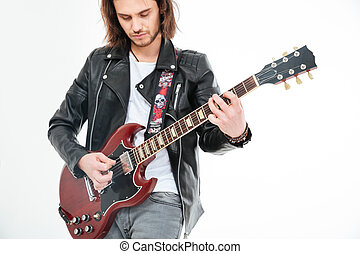 Attractive man with long hair playing electric guitar using...