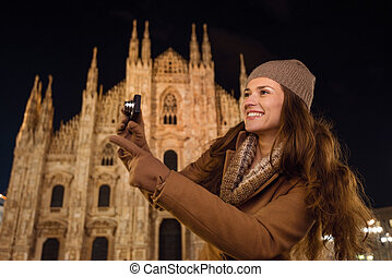 Woman with photo camera pointing on something near Duomo,...