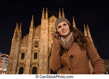 Young woman talking cell phone near Duomo in evening, Milan...