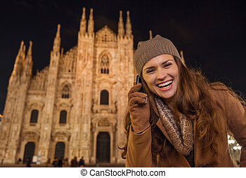 Smiling woman talking cell phone near Duomo in evening,...