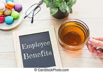 Concept Employee Benefits message on wood boards. Macaroons...