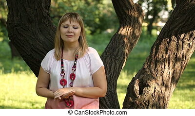 portrait of speaking woman on nature - Blonde womna tell...
