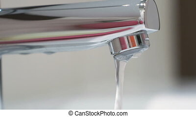 A thin stream of water pours from the faucet in the...