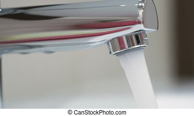 A strong jet of water pours from the faucet in the bathroom...