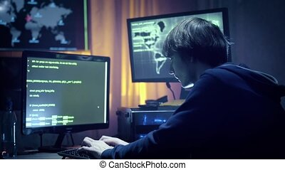 Hacker in hooded jacket using computer at table HD