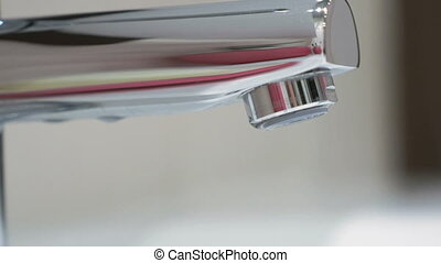 Transparent drop of water falls from the faucet. Slow...