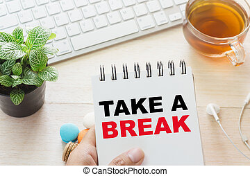 Man holding TAKE A BREAK message on book and keyboard with a hot cup of tea, macaroon on the table. Can be attributed to your ad.