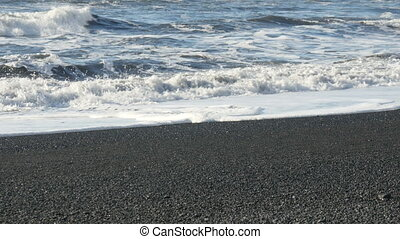 Waves breaking at black sand beach - Waves breaking at the...