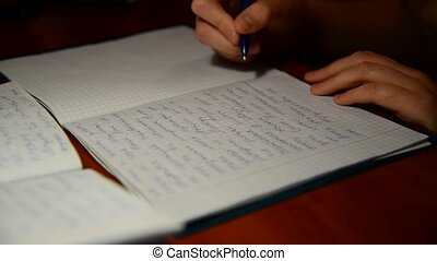 boy writes in notebook homework on Russian language - The...