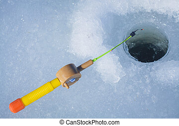 Ice-hole and fishing rod for winter fishing.  river