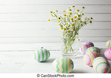 Bouquet of chamomiles in a glass vase and easter eggs in pastel color on white wooden table
