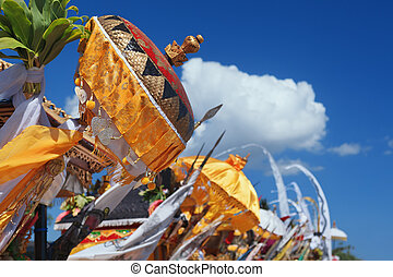 Traditional Balinese ceremonial umbrellas and flags on beach...