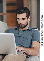 Modern blogger Handsome young man using his laptop while...