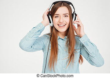 Happy charming young woman in headphones listening to music