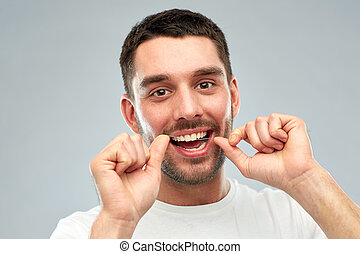 man with dental floss cleaning teeth over gray - health...