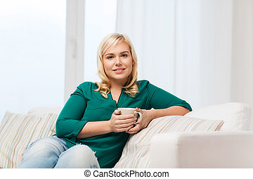 happy woman with cup of tea or coffee at home - people and...