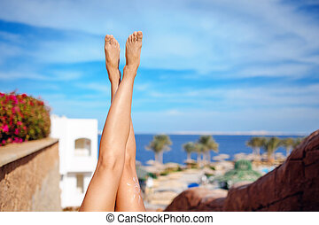 Beautiful legs of girl on a background of blue sky