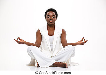Pacified pretty african woman sitting and meditating in...