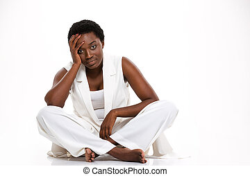 Tired african woman sitting with legs crossed and having...