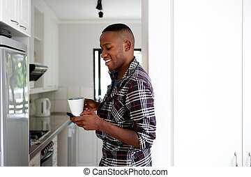 Young man in the kitchen with coffee using cell phone