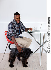Young african man sitting at home with his pet dog and laptop