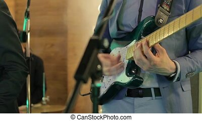 Man in suit playing on electric guitar