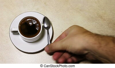 Stirring the coffee in the cup