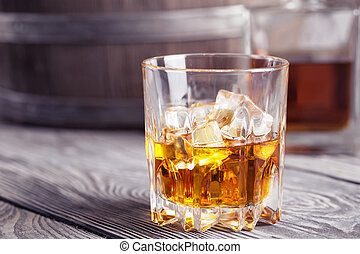 Bright faceted glass of whiskey on background barrel and...