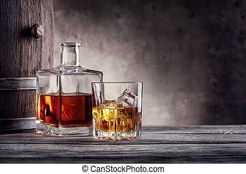 Square decanter and a glass of whiskey with ice on...