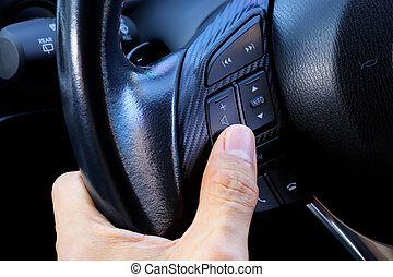 Close up interior modern car button on  steering wheel with driver hand