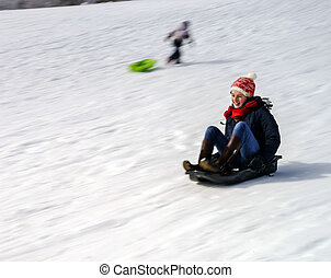 Teenage girl sledding from the hill