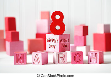 Womans Day - March 8 message with red and pink wooden blocks