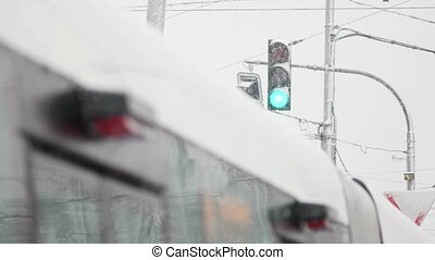 Green Traffic Light - Traffic light during snowstorm showing...