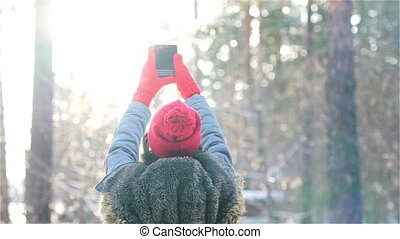girl make a selfi in winter in sunset