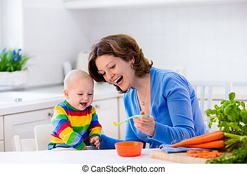 Mother feeding baby first solid food