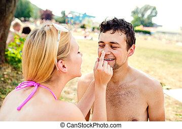 Woman in bikini putting sunscreen on nose of man - Woman in...
