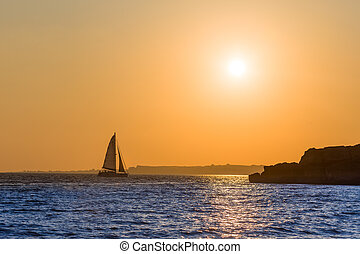 Sailor 's sunset - Distant boat with sails driven by the...